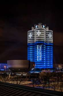 """The BMW Group has delivered more than 100,000 electrified vehicles to customers worldwide in 2017. All as promised at the beginning of the year. The picture is an eye-catching light installation transformed the BMW Group headquarters. On the world-famous """"Four-Cylinder"""" in the north of Munich. For this was on the evening of 18 December 2017 into a battery. (12/2017)"""